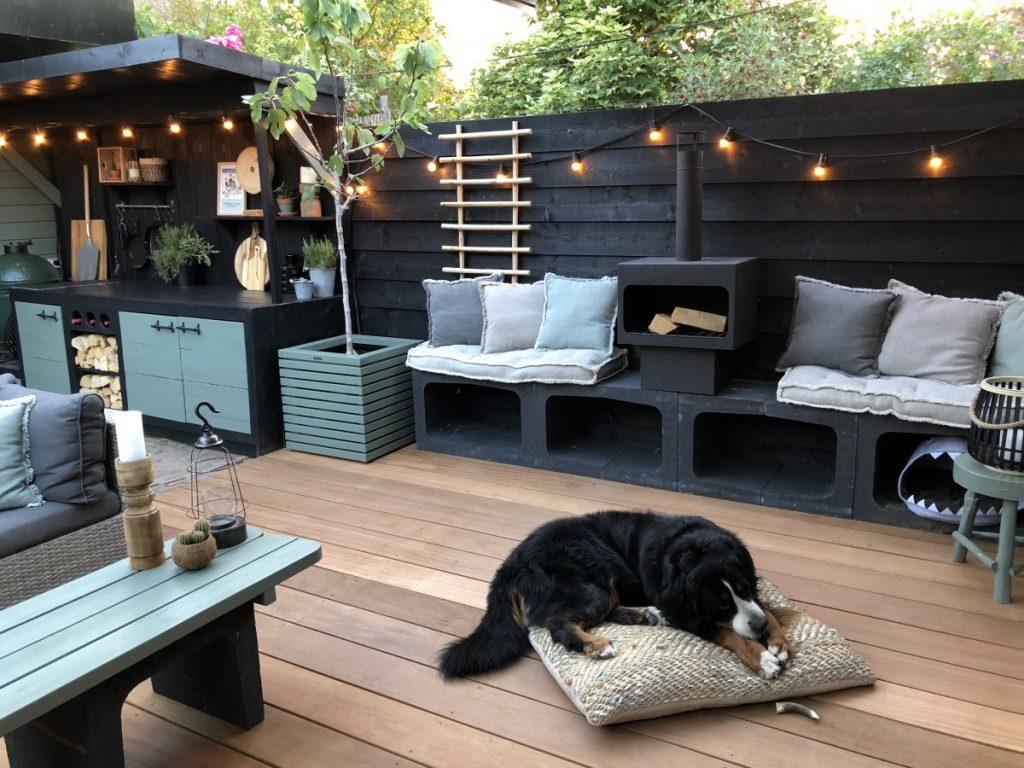 houten vlonder in tuin met zwarte schutting en buitenkeuken