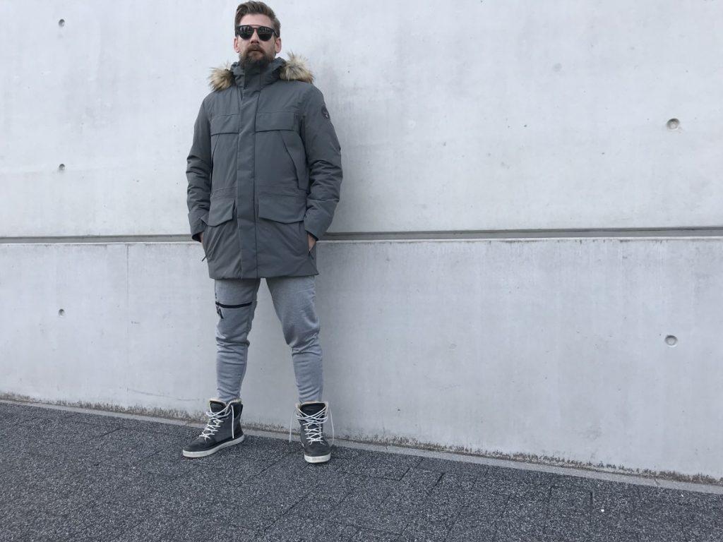 Jan willen draagt een grijze joggingbroek, grijze jas en grijze schoenen