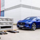 Blauwe Jaguar I-Pace voor een stapel aluminium