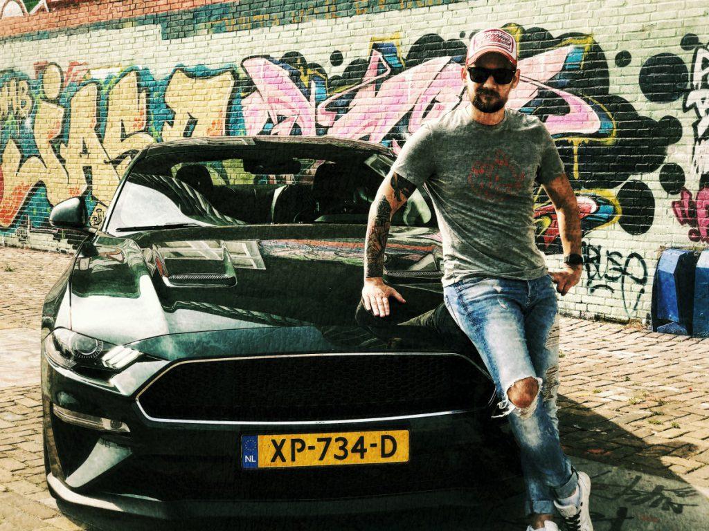 Een rauwe foto van Jan Willem Huffmeijer bij de Mustang